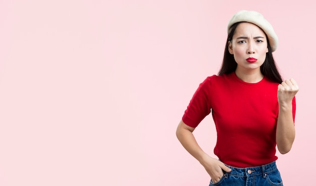 Femme aux lèvres rouges montrant son poing