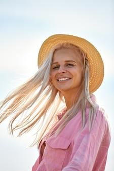 Femme aux longs cheveux blonds et un chapeau de paille dans un champ de blé