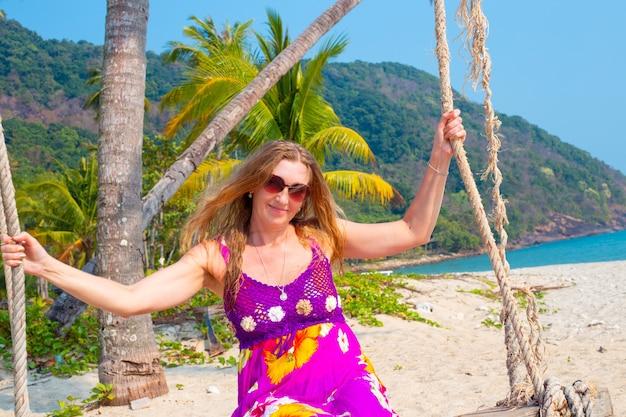 Femme aux longs cheveux blonds dans une robe lumineuse avec des fleurs se balance sur une balançoire au bord de la mer, des vacances romantiques inoubliables sur une île tropicale