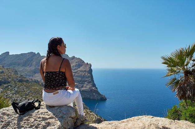 Femme aux longs cheveux brune posant un jour de printemps avec des lunettes de soleil, assis sur la falaise