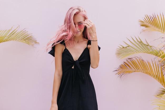 Femme aux longs cheveux roses debout à côté de palmiers exotiques en studio.
