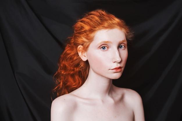 Femme aux longs cheveux roux bouclés se sont réunis en queue de cheval sur fond noir. fille rousse avec une peau pâle, des yeux bleus, une apparence inhabituelle sans maquillage. beauté naturelle. fille de l'ère de la renaissance