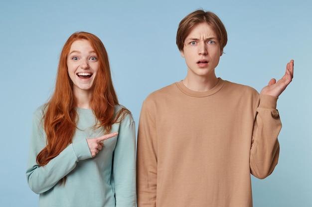 Femme aux longs cheveux roux rit et montre du doigt avec son index le gars qui se tient avec une expression perplexe