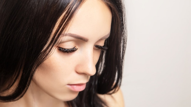 Femme aux longs cils bruns. portrait de beauté féminine. extensions de cils, soins, beauté et spa