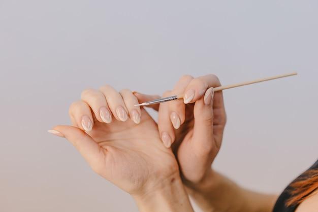 Une femme aux mains bien coiffées se couvre les ongles avec du gel-vernis à l'aide d'un pinceau fin sur fond blanc.