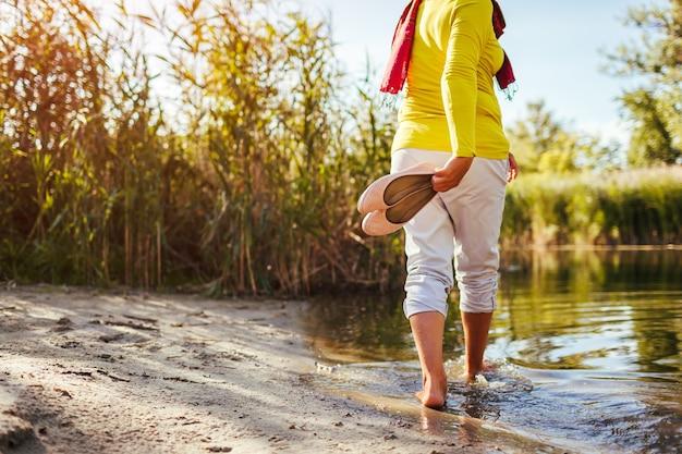 Femme aux pieds nus d'âge moyen marchant sur la rive du fleuve le jour du printemps. dame âgée s'amusant dans la forêt en profitant de la nature.