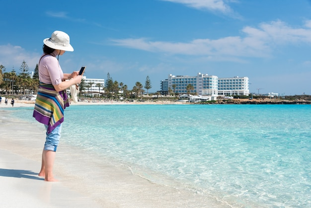 Femme aux pieds nus avec chapeau sur la plage, prendre des photos de la mer avec smartphone. concept de vacances d'été, vacances, voyages et personnes