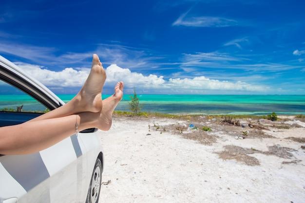 Femme aux pieds nus depuis la fenêtre d'une voiture sur une plage tropicale