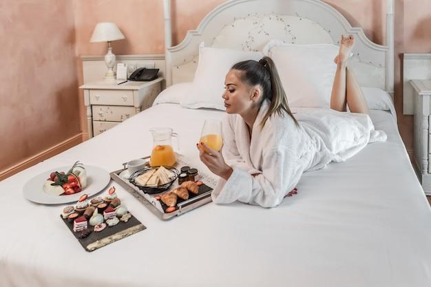 Femme aux pieds nus prenant son petit déjeuner au lit