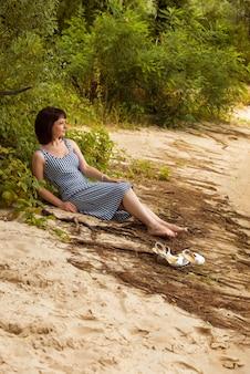 Femme aux pieds nus sur la rive d'un lac