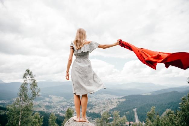 Femme aux pieds nus se tient à la pierre dans les montagnes et agitant une couverture rouge