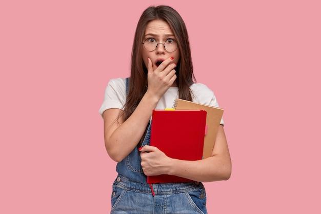 Une femme aux taches de rousseur émotive couvre la bouche, a une scène effrayante, porte un bloc-notes, porte un t-shirt blanc décontracté et une salopette