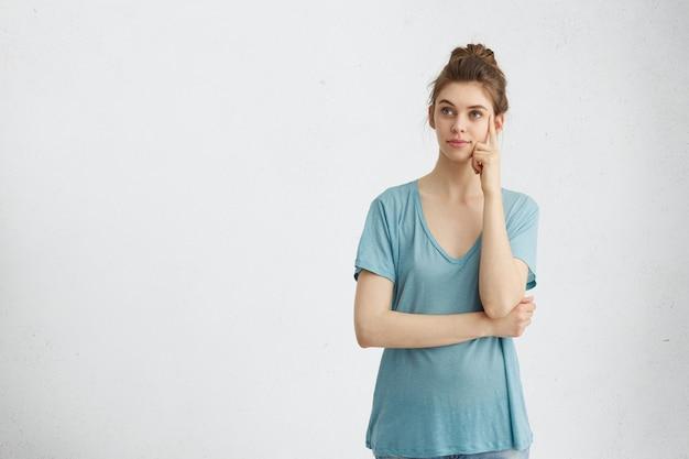 Femme aux yeux bleus ayant une expression pensive pensant