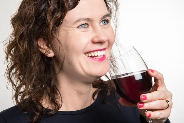 Femme aux yeux bleus buvant un verre de vin