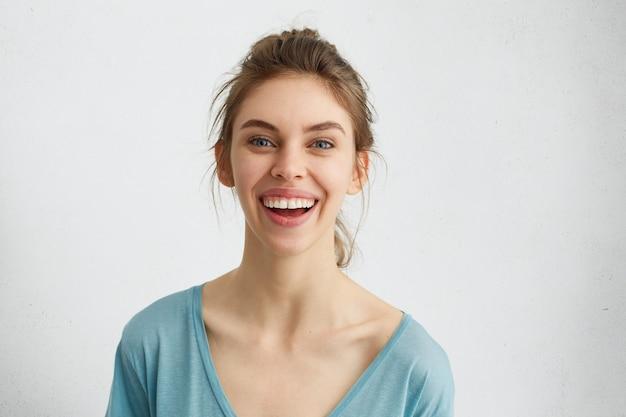 Femme aux yeux bleus et une peau saine souriant