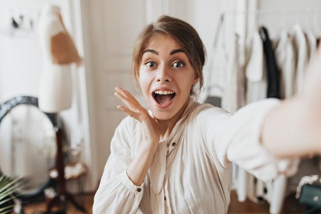 Femme aux yeux bleus surpris posant au bureau