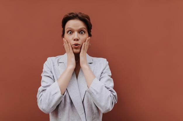 Femme aux yeux bruns en costume gris surpris en regardant la caméra. jolie fille aux cheveux courts en veste surdimensionnée pose sur fond isolé