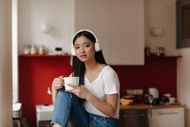 Femme aux yeux bruns en t-shirt blanc et écouteurs massifs regarde à l'avant, posant avec tasse sur fond de cuisine