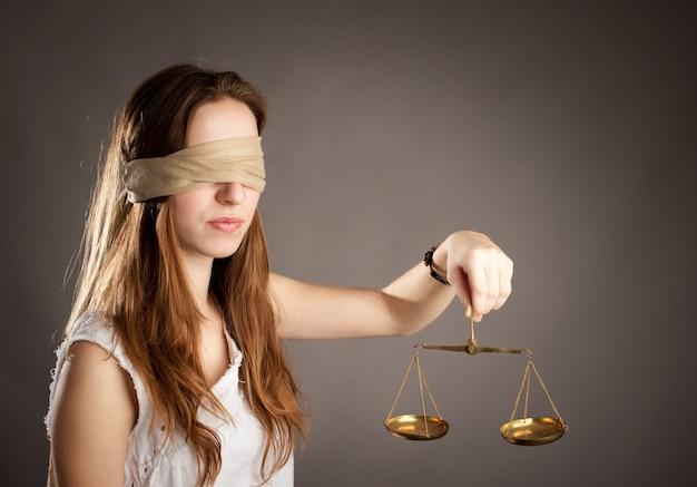 Femme aux yeux couverts, tenant une balance de la justice