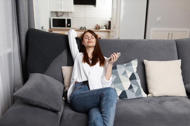 Femme aux yeux fermés au repos à la maison sur un canapé confortable avec un téléphone dans ses mains.