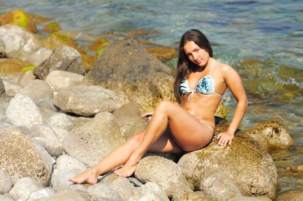 Femme aux yeux fermés, les bras levés et près de la tête, en maillot de bain assis sur des pierres au bord de la mer