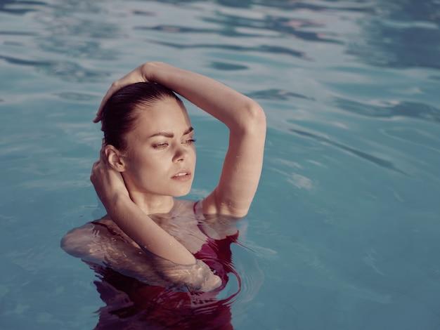 Femme aux yeux fermés dans la piscine les mains sur le plaisir de la tête glamour