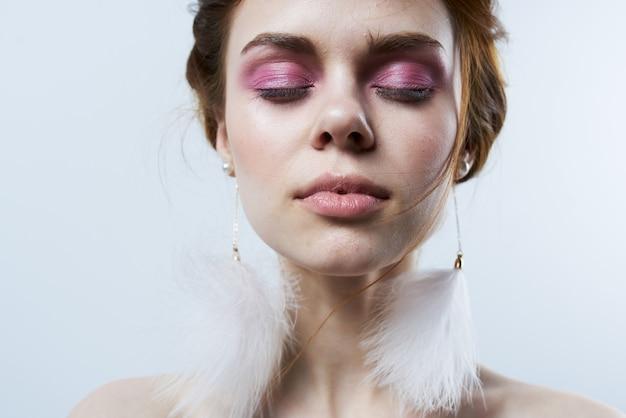 Femme aux yeux fermés épaules nues maquillage lumineux luxe gros plan