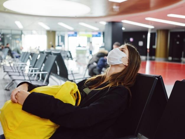 Femme aux yeux fermés d'un masque médical en attente d'un vol à l'aéroport