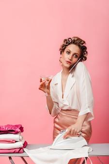 Femme aux yeux gris avec des bigoudis parlant au téléphone, appréciant le martini et le repassage t-shirt blanc