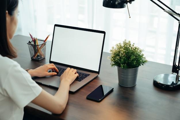 La femme avait à l'aide d'un écran blanc d'ordinateur portable et de papeterie sur la table de la maison.