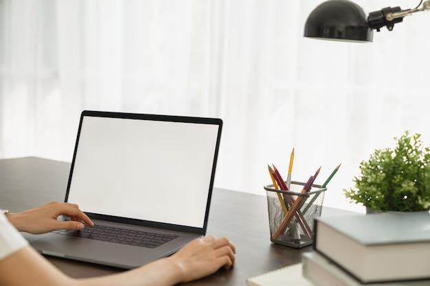 La femme avait à l'aide d'un écran blanc d'ordinateur portable et de papeterie sur la table.
