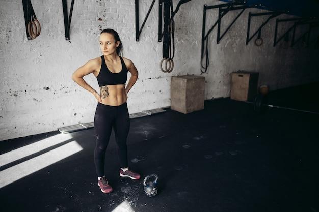 Femme, avant, lourd, kettlebell, séance entraînement, gymnase