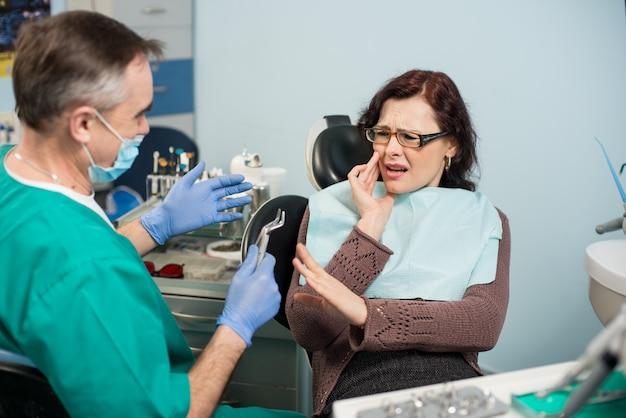 Femme, avoir mal aux dents, toucher la joue avec la main à la clinique dentaire. dentiste principal essayant d'aider avec un outil dentaire - décapant