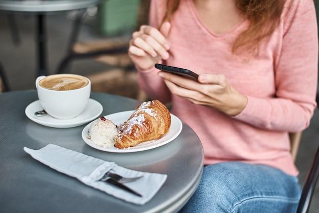 Femme, avoir, petit déjeuner, dans, a, café, et, utilisation, smartphone