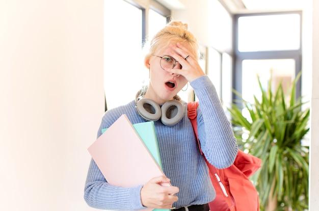 Femme ayant l'air choquée, effrayée ou terrifiée, couvrant le visage avec la main et regardant entre les doigts