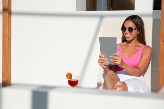 Femme ayant un appel vidéo sur sa tablette pendant ses vacances