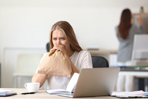 Femme ayant une attaque de panique sur le lieu de travail