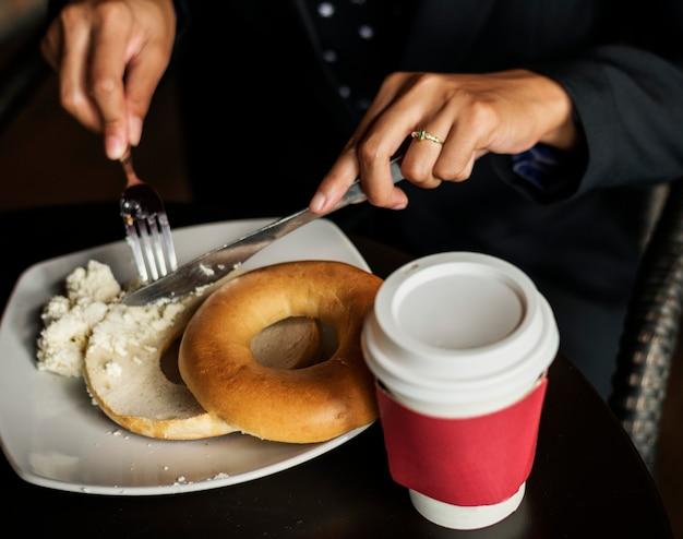 Femme ayant un bagel pour le petit déjeuner