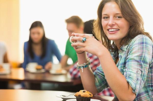 Femme ayant un café et un muffin au café