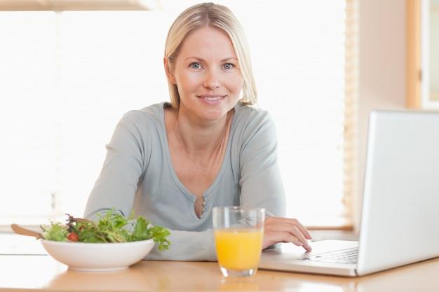 Femme ayant un déjeuner sain tout en travaillant sur son carnet