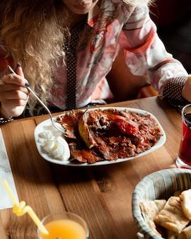 Femme ayant un donateur turc d'iskender avec sauce tomate et yaourt.