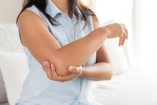 Femme ayant une douleur au coude blessé. concept de soins de santé et douleur au bras.