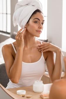 Femme ayant une journée de détente et à l'aide de crème pour le visage