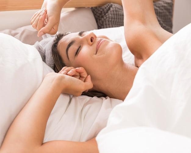 Femme ayant une journée de détente au lit