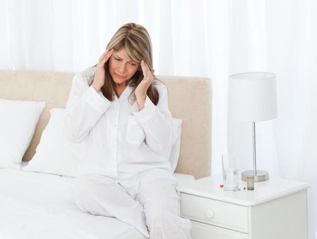 Femme ayant un mal de tête sur son lit