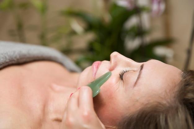 Femme ayant un massage facial gua sha avec masseur de pierre de jade naturel