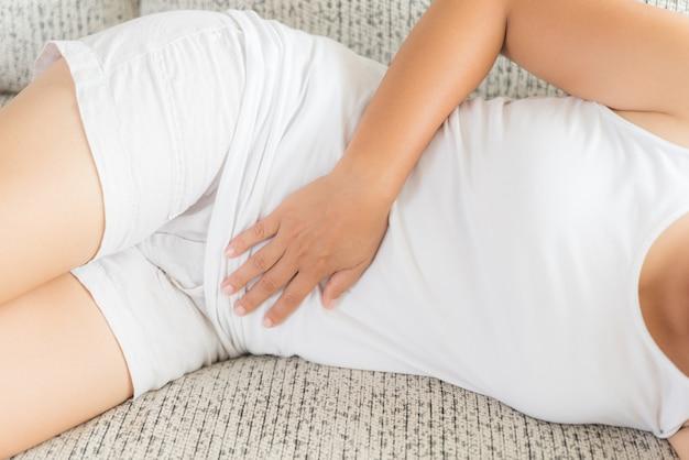 Femme ayant des maux d'estomac douloureux assis sur un canapé à la maison. gastrite chronique