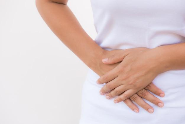 Femme ayant des maux d'estomac douloureux sur fond blanc. concept de ballonnement de l'abdomen.