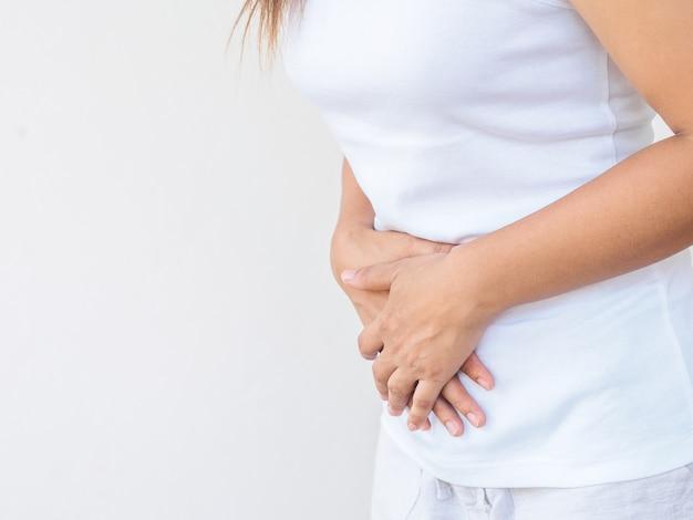 Femme ayant des maux d'estomac douloureux sur fond blanc