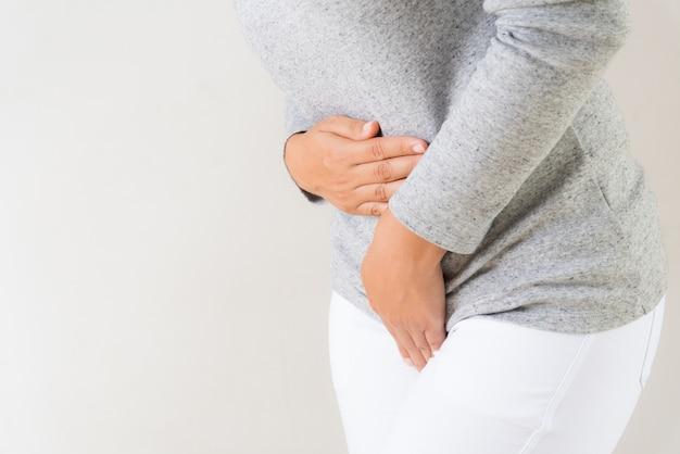 Femme ayant des maux d'estomac douloureux avec les mains appuyant sur son entre-jambes et son abdomen inférieur.